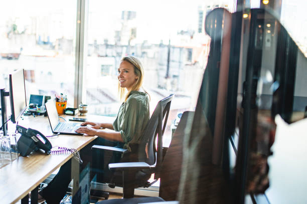 Smiling Blonde Businesswoman Working on Laptop in Office stock photo