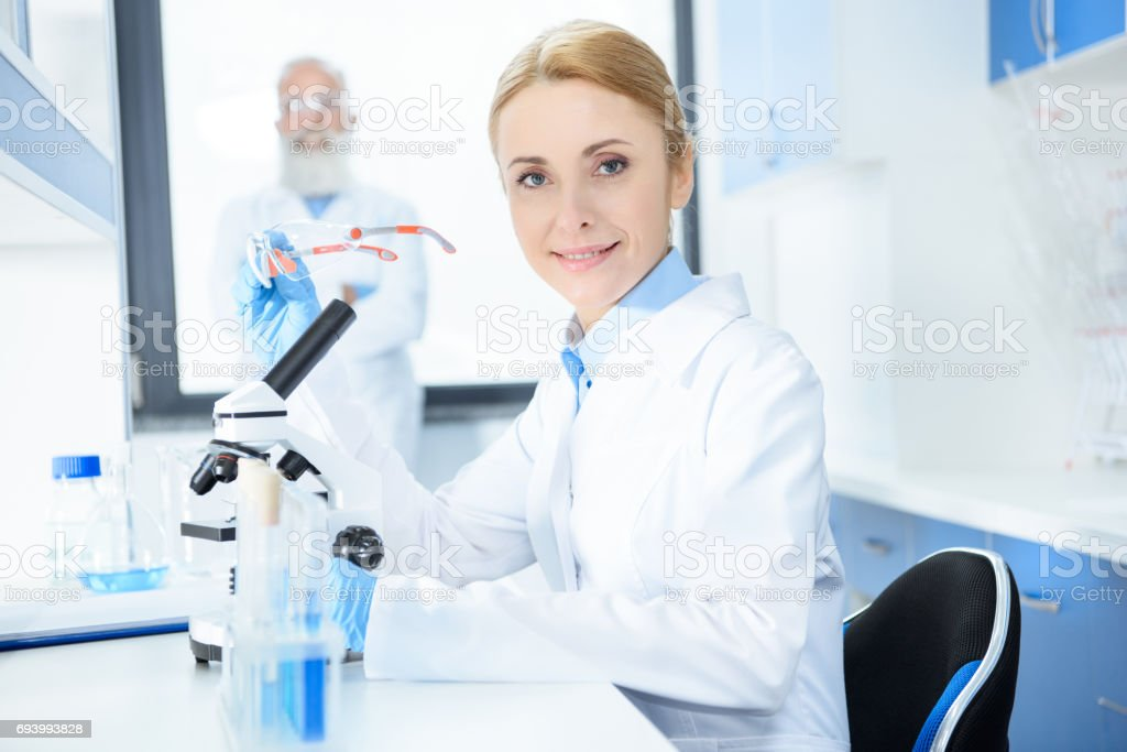 Souriant chimiste blonde en blouse blanche tenant des lunettes et  travaillant au microscope photo libre de 10f0ef1be20e