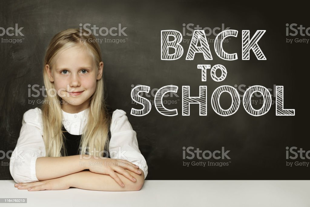 Smiling blonde child girl thinking on chalkboard. Back to school...