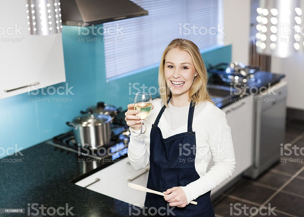 Smiling blonde cooking in elegant kitchen, toasts with white wine royalty-free stock photo