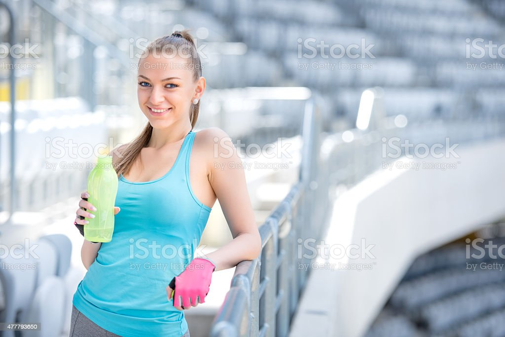 Smiling blonde fitness woman drinking water after complete outdoor workout stock photo