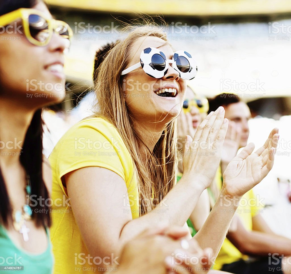 Smiling blonde football fan and friends supporting Brazil stock photo