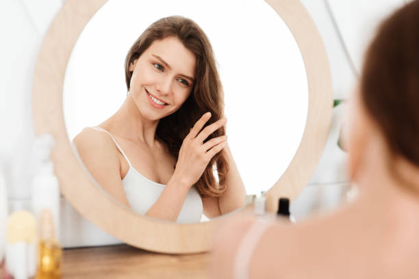 Smiling blonde girl looking at mirror, touching her hair stock photo