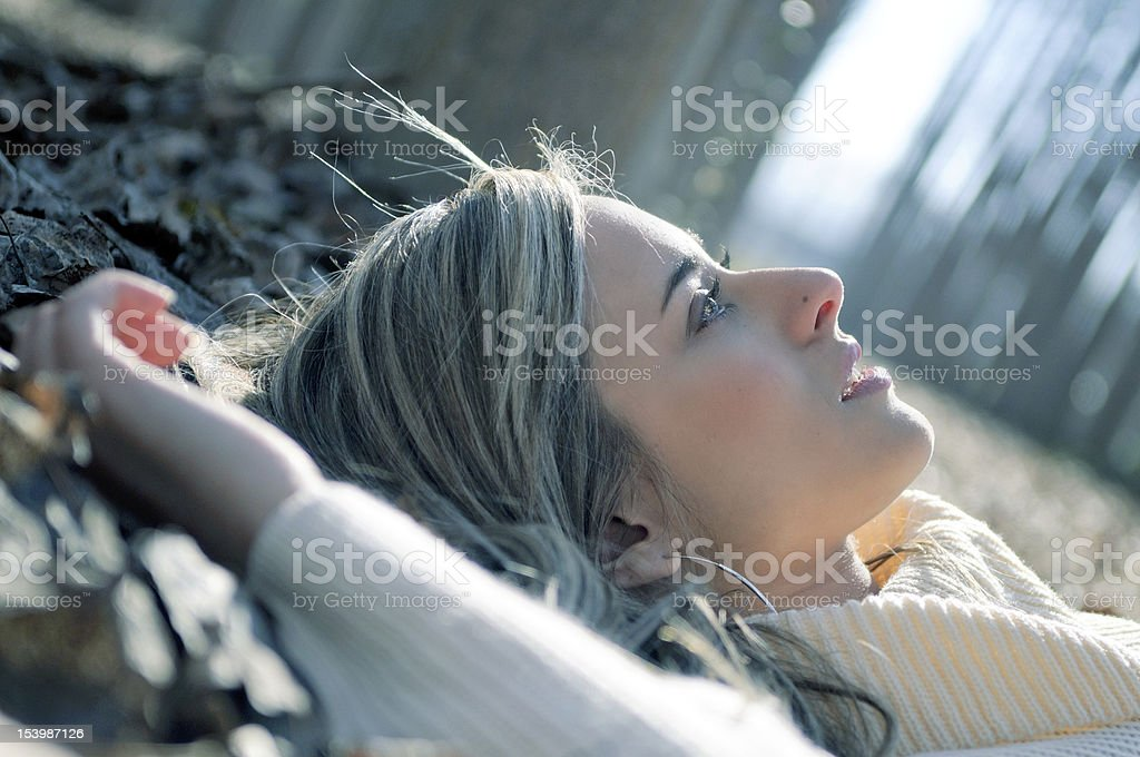 Smiling blonde girl lying on leaves in a forest stock photo