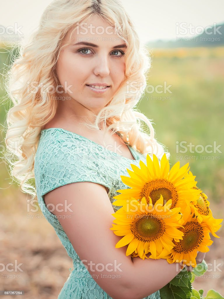 smiling blonde girl outdoors with sunflowers in hands royalty-free stock photo