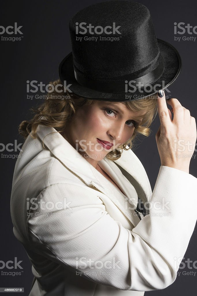 Smiling blonde in white tux touching top hat. royalty-free stock photo
