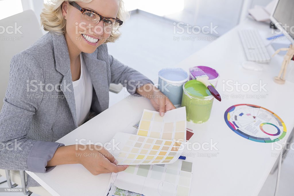 Smiling blonde interior designer holding colour charts royalty-free stock photo