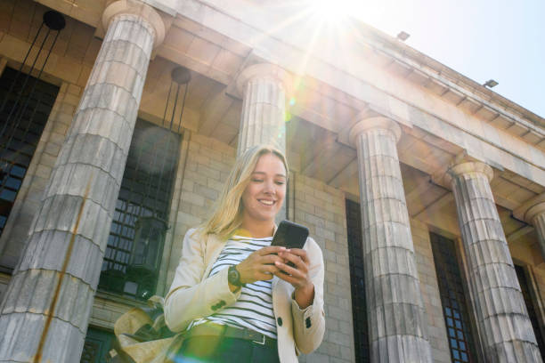 Smiling Blonde Law Student with Backpack and Smart Phone stock photo