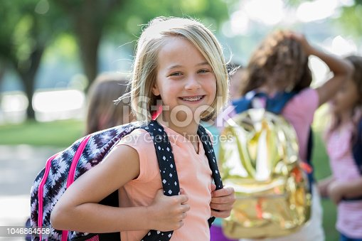 A short haired blonde middle school girl is smiling and holding her backpack ready for school