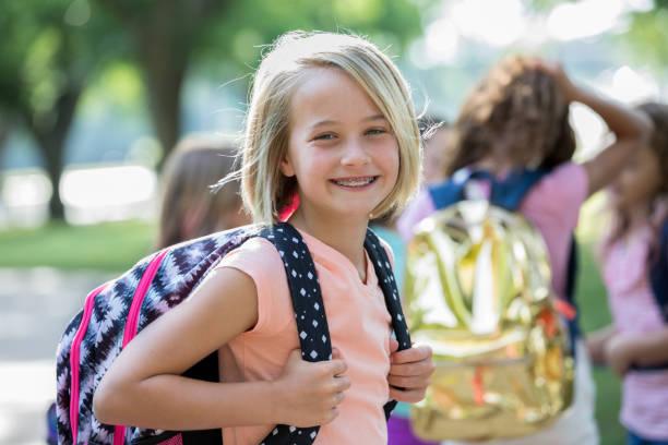 smiling blonde little girl ready for school - cartella scolastica foto e immagini stock