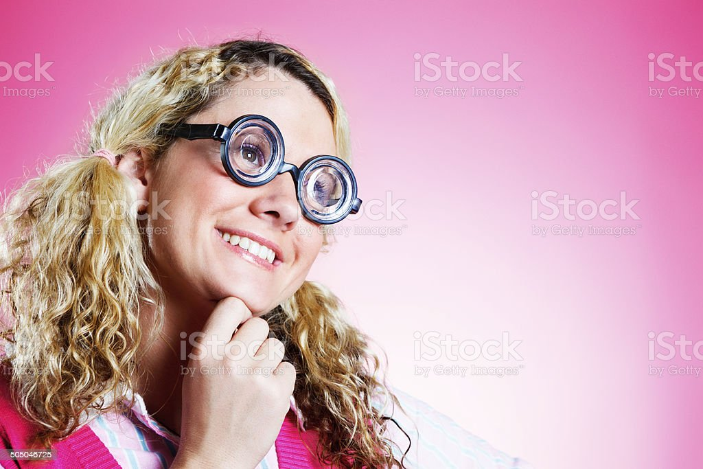 Smiling blonde nerd in horn-rimmed glasses is happy with life stock photo
