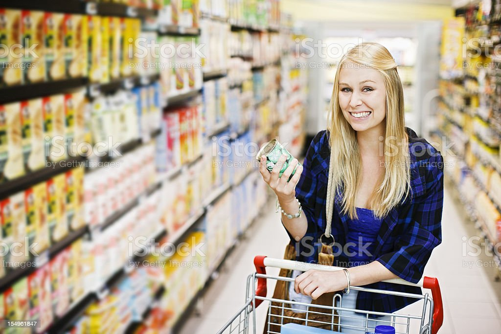 Smiling blonde shopper selects canned peas in supermarket royalty-free stock photo