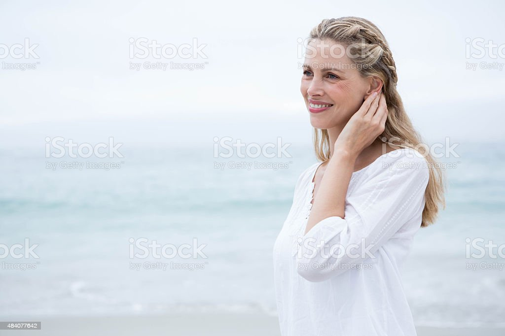 Smiling blonde standing by the sea stock photo