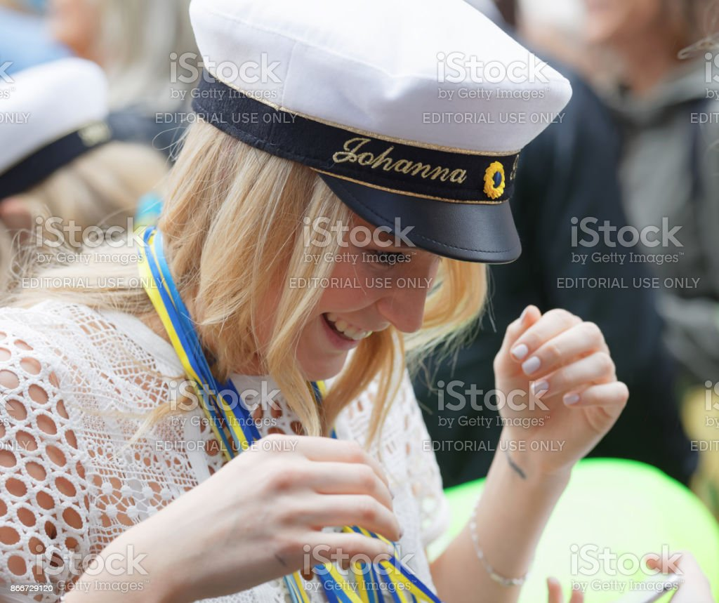 Smiling blonde students girl wearing white graduation cap and white dress stock photo