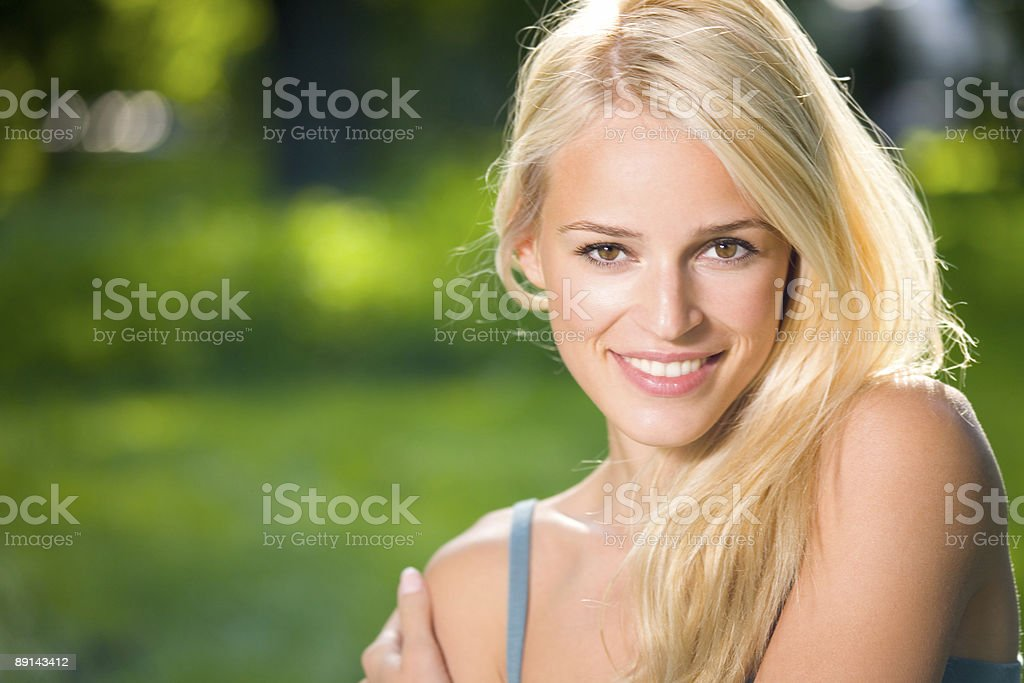 Smiling blonde woman against a blurred green background royalty-free stock photo