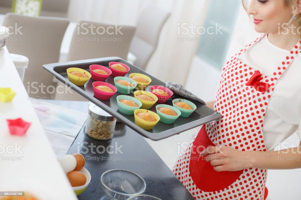 Smiling blonde woman cooking cupcakes in kitchen foto stock royalty-free