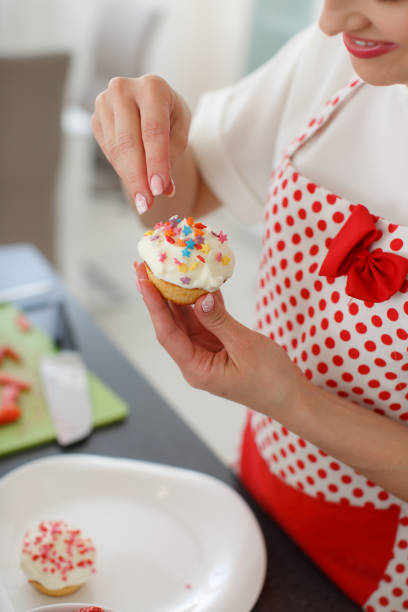 smiling blonde woman cooking cupcakes in kitchen stock photo female baker hands decorating