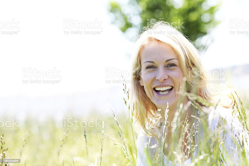 Smiling blonde woman sitting in meadow royalty-free stock photo