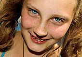 smiling blue-eyed girl in bright sun light