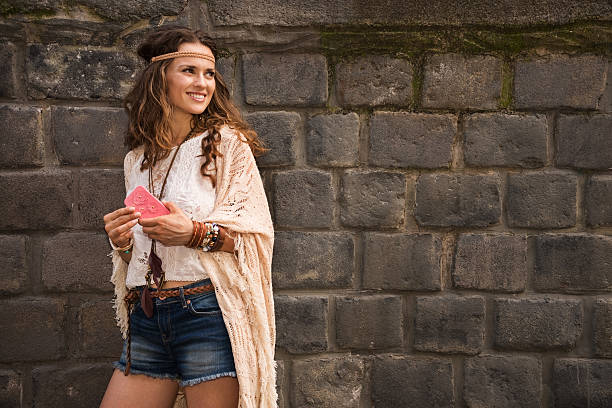 smiling boho woman near stone wall looking on copy space - hippie fashion stock photos and pictures