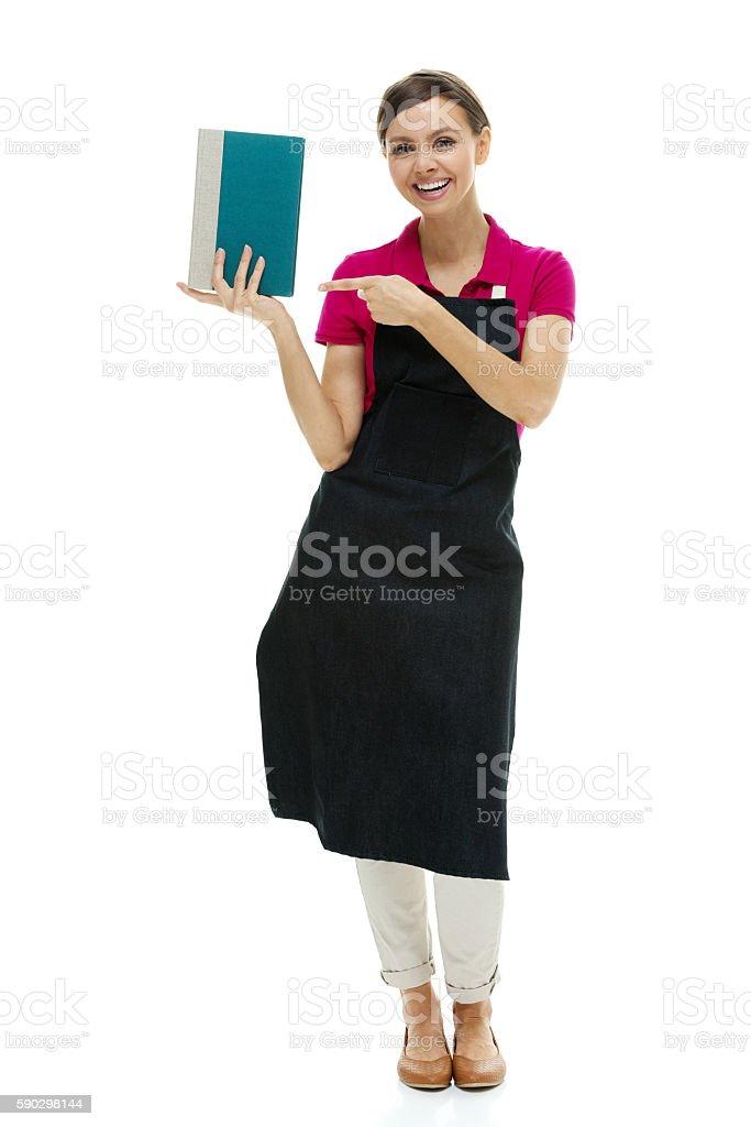 Smiling bookseller pointing at book royaltyfri bildbanksbilder