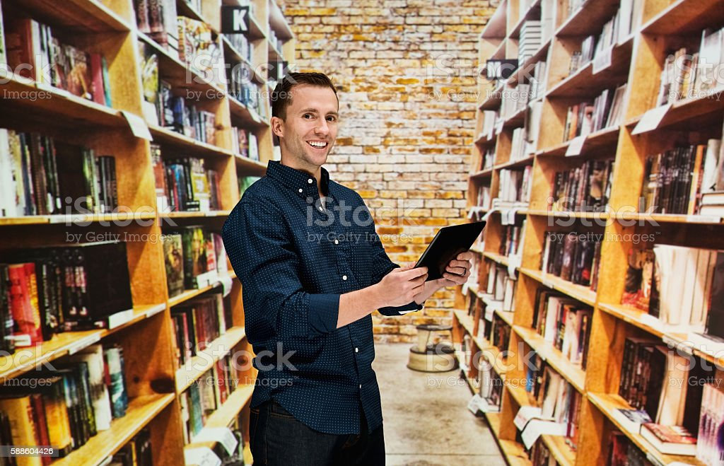 Smiling bookseller using tablet stock photo