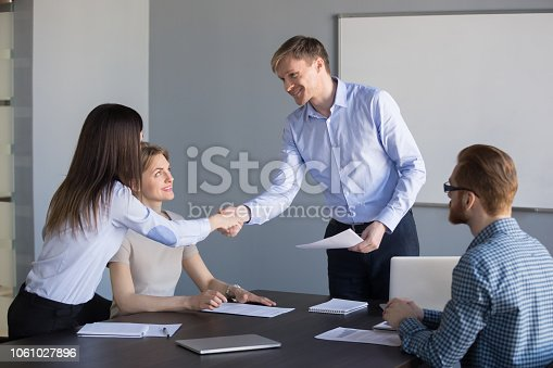 istock Smiling boss handshaking employee thanking for good work or promoting 1061027896