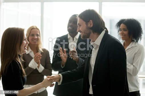 istock Smiling boss handshaking happy female employee promoting rewarding excited worker 958531486