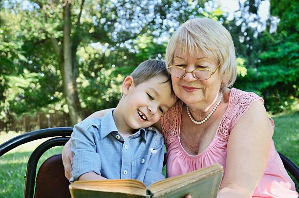 Lächelnde Junge mit seiner Großmutter Sitzbereich im Park – Foto