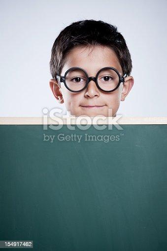 istock Smiling boy behind a chalkboard. 154917462