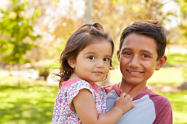 Smiling boy carrying his little sister looks to camera stock photo