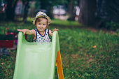 Cute small boy enjoying on a slide in nature.