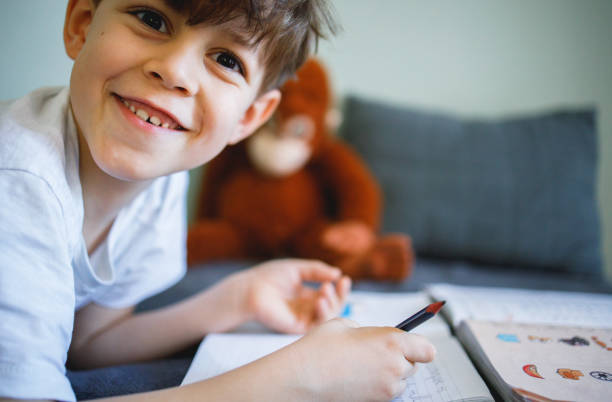 Smiling boy doing homework stock photo