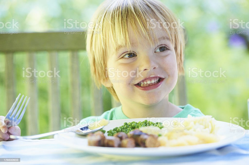 Smiling boy eating plate of food stock photo