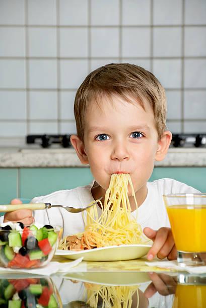 Lächelnde junge Essen spaghetti und hält der Gabelung links – Foto