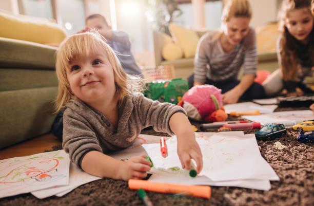 niño sonriente que se divierten al colorear la sala de estar. - niñera fotografías e imágenes de stock