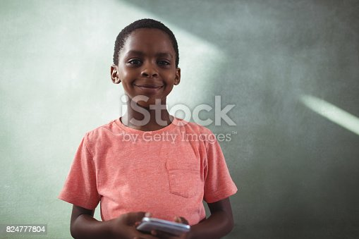 istock Smiling boy holding cellphone against greenboard 824777804