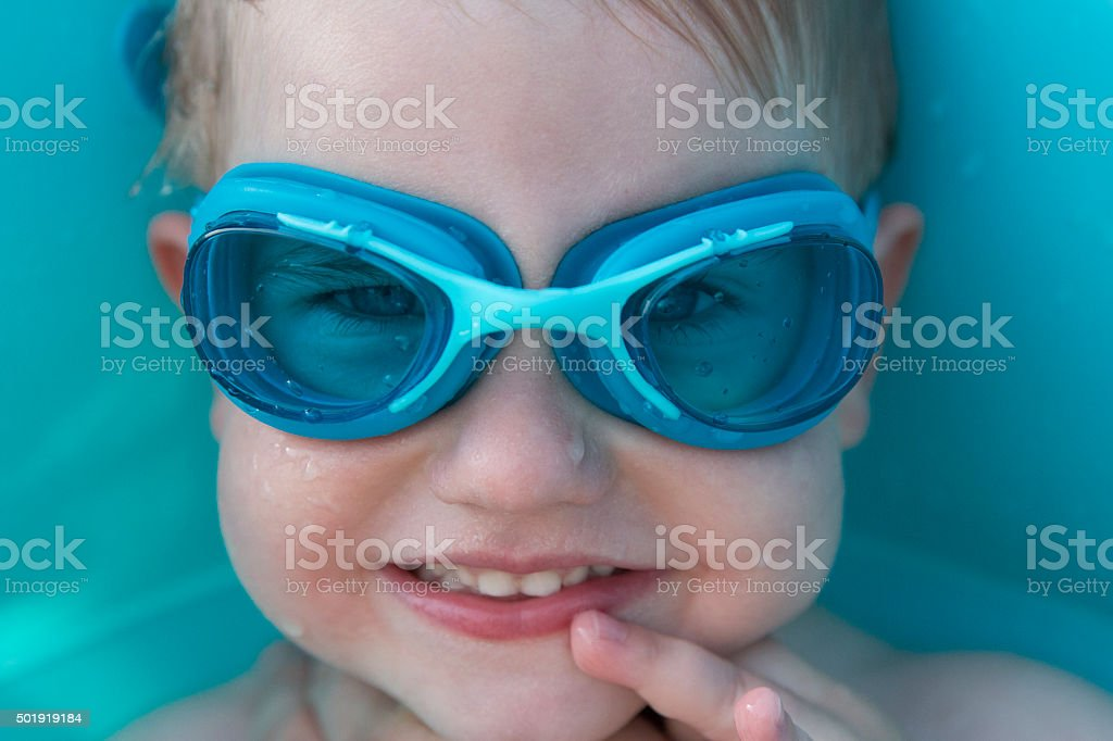 smiling boy in blue swimming goggles stock photo