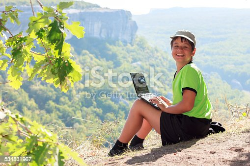 istock Smiling boy in green t-shirt with netbook on mountain 534831967