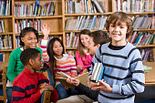 istock Smiling boy in school library holding books by reading group 183868094