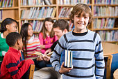 istock Smiling boy in school library holding books 183415045