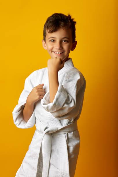 niño con kimono blanco combatiente sonriente - kárate fotografías e imágenes de stock