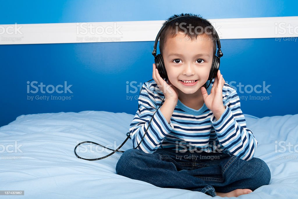 Smiling boy listening to headphone in bed royalty-free stock photo