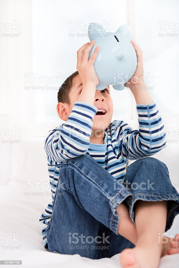 Smiling boy looking inside piggy bank royalty-free stock photo