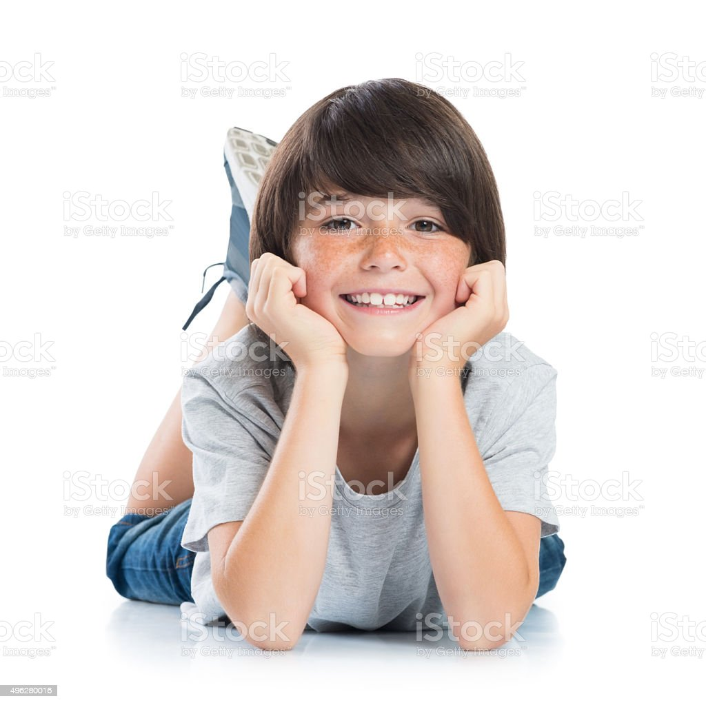 Smiling boy lying on floor stock photo