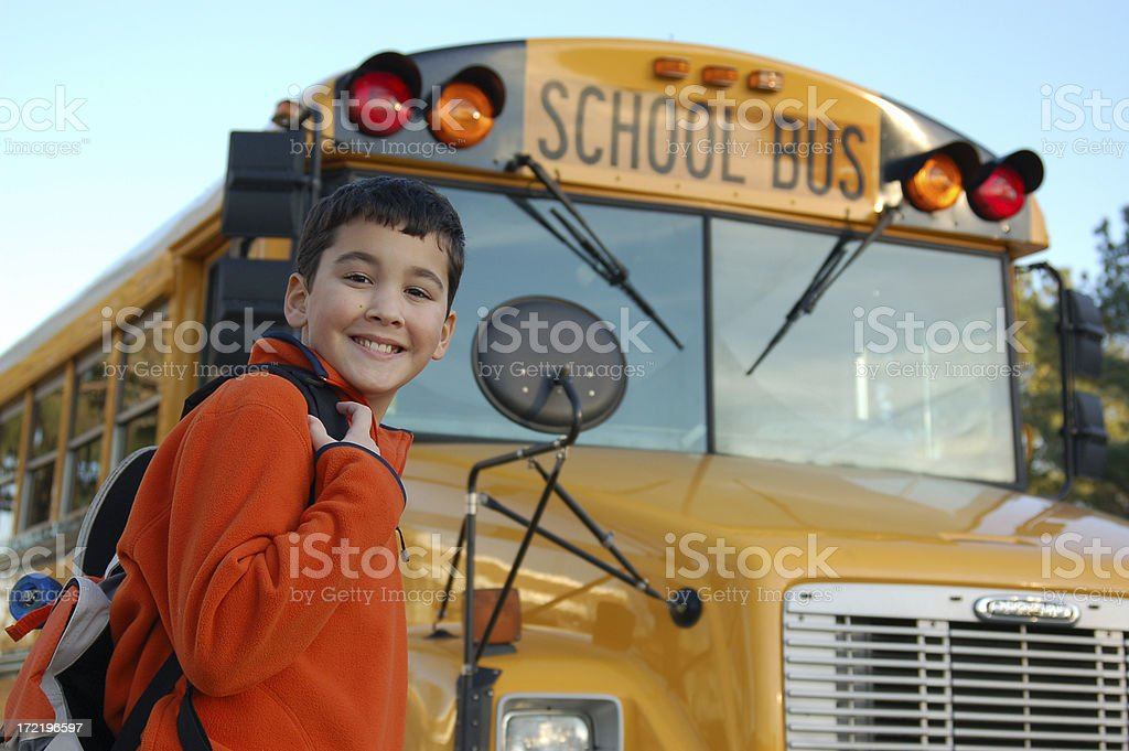 Smiling boy near the school bus stock photo