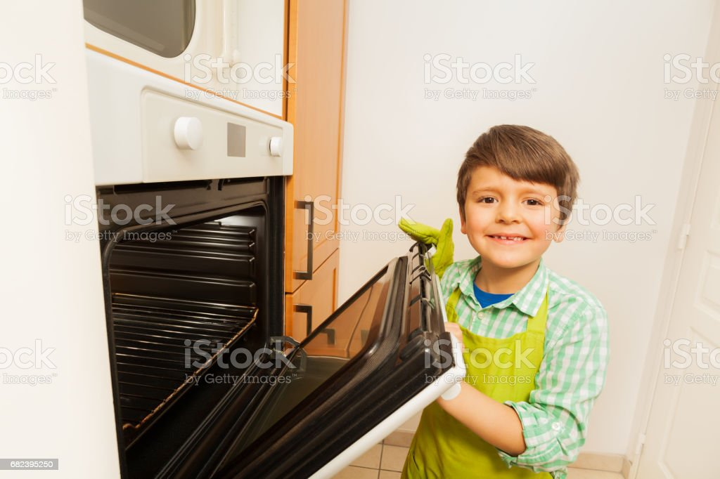 Smiling boy opening hot oven door in the kitchen royalty-free stock photo