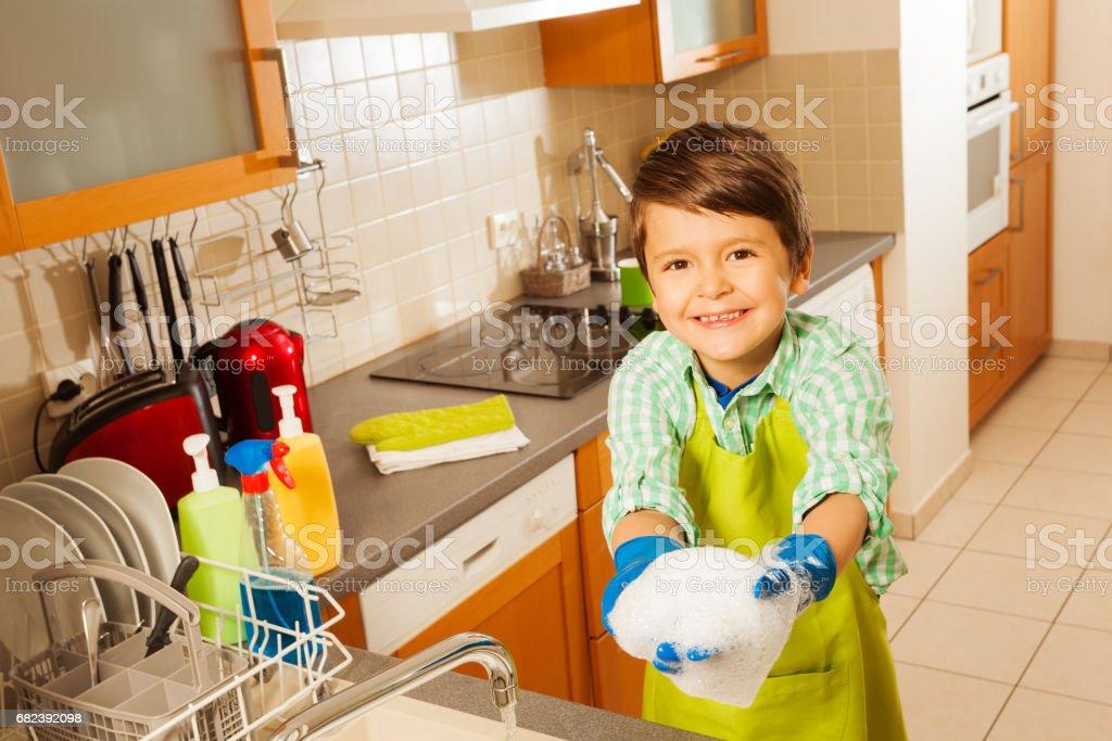 Garçon souriant, jouant avec de la mousse pendant le lavage de la vaisselle photo libre de droits