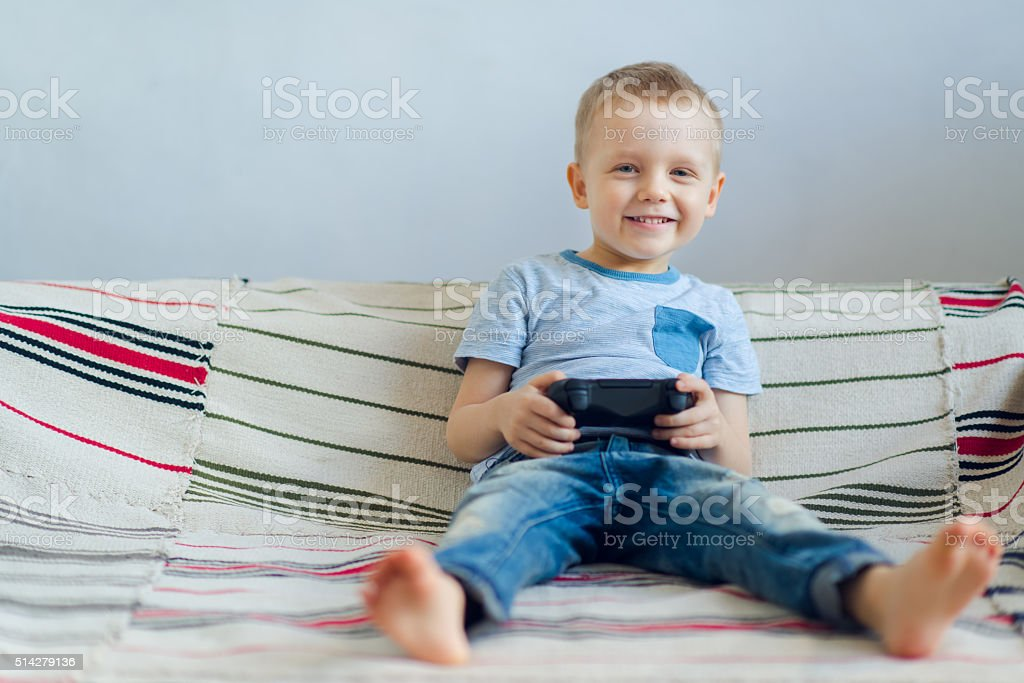 Smiling boy playing with playstation stock photo