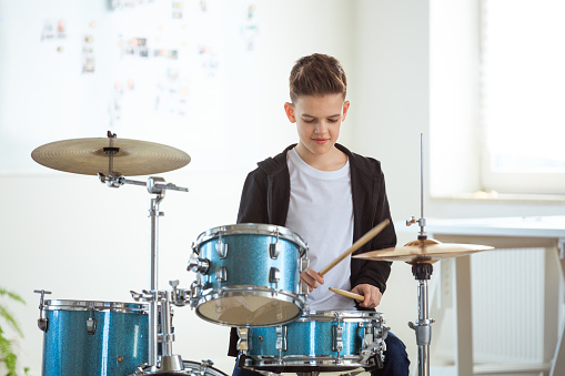 Smiling Boy Practicing Drum In Conservatory Stock Photo - Download Image Now
